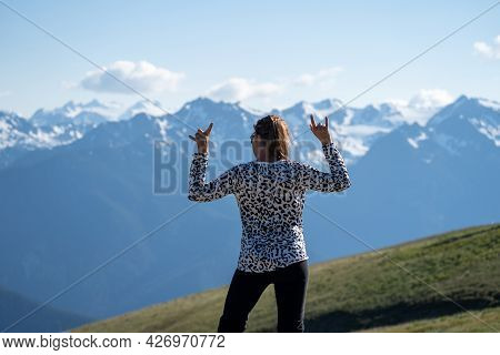 Young Adult Woman With Back Facing The Camera, Rocks Out And Headbangs At Hurricane Ridge In Olympic