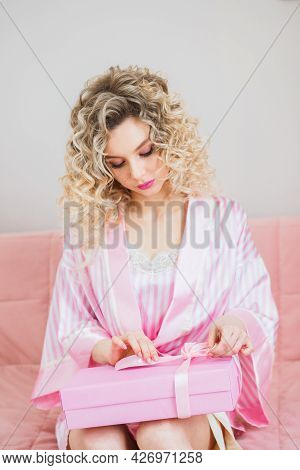 Curly Blonde Girl In Pink Pajamas Unwraps A Gift For A Bachelorette Party.