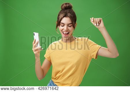 Cool And Stylish Happy Woman With Tattoo And Gap Teeth In Yellow T-shirt Dancing Joyfully Listening