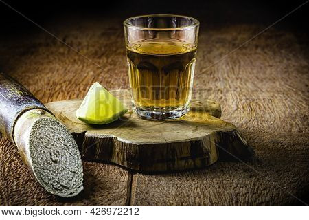 Glass Of Cachaça, A Brazilian Drink Distilled From Sugar Cane, Served With Lemon, Also Called Pinga,