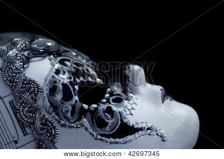 Venetian mask over black background.