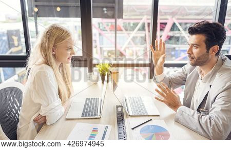 Concentrated Man And Woman Workers Sit At Office Desk Negotiating Using Laptop Discussing Ideas, Div