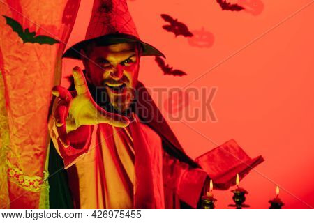 Scary Face. Best Ideas For Halloween. Halloween Redhead Man With A Magic Book And Magic Lights. Hall