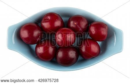 Washed Ripe Plums In Light-blue Oval Plate Isolated On White Background. Top View