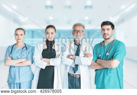 Portrait Group Of Doctors With Stethoscope In Medical Uniform Arms Crossed Posing In Front Of Examin