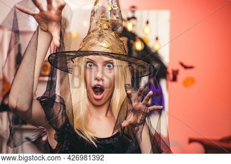 Beautiful Young Surprised Woman In Witches Hat And Costume Pointing Hand - Showing Products. Beautif