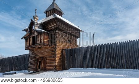 The Old Chapel Was Built From Unpainted Logs. On The Roof There Is A Dome, A Cross. Wooden Fence Alo