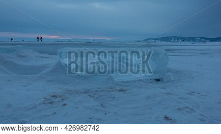 Twilight On A Frozen Lake. In The Foreground Is A Glittering Ice Floe Surrounded By Snow. In The Dis