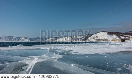 The Blue Water Of The Ice-free River Is Rippled. At The Coast There Is Ice With Cracks And Hummocks.