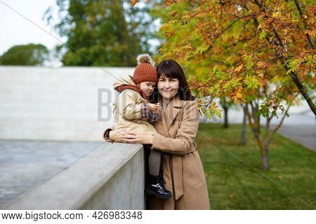 Portrait Of Young Attractive Woman Posing With His Little Daughter In Autumn Park
