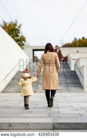 Family, Motherhood, Love And Care Concept - Back View Of Happy Mother And Her Little Daughter Walkin
