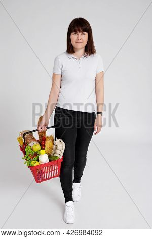 Full Length Portrait Of Young Woman With Shopping Basket Full Of Products Walking Over White Backgro