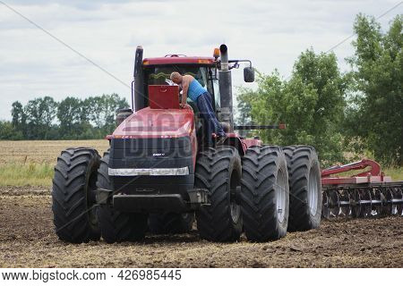 Tractor Driver Near A Large Red Tractor. A Farmer On A Tractor Prepares Land For A Seeding, Tractor