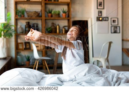 Ten-year-old Girl Woke Up And, Stretching. She Stretched Her Arms Up And Enjoys The Day Off.
