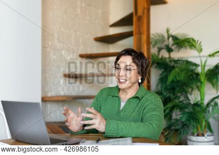 Smiley Senior Woman In Front Of Laptop Monitor During Online Video Call. Online Working.