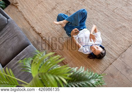 Teenage Girl Lying On The Floor During An Online Video Call On A Smartphone. She Says Hi And Waves H