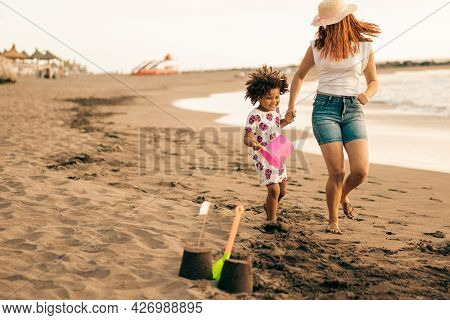 Caucasian Mother And African Daughter Having Fun Running On A Sandy Beach. Mum And Son Building A Sa