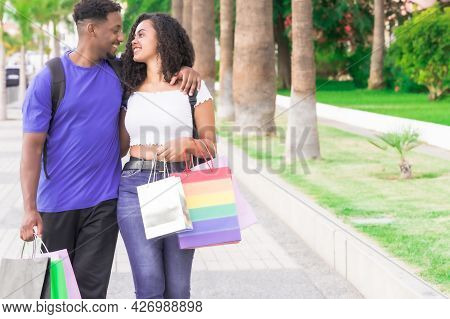 Cheerful Couple In Love Spends Time Together, They Walk Through The City After Mall Center On A Summ