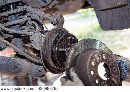 Gloved Hands Remove Or Slide The Wheel Rim Onto The Hub Of The Old Car. In The Garage, A Man Changes