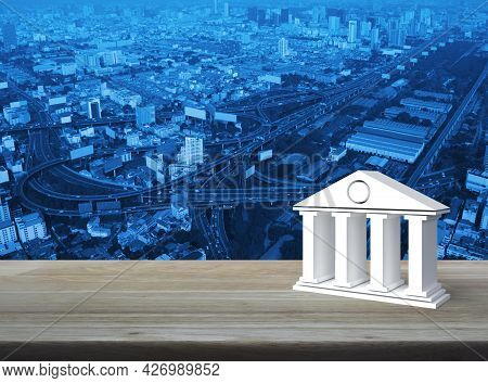 Bank 3d Icon On Wooden Table Over Modern City Tower, Street, Expressway And Skyscraper, Business Ban