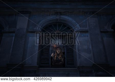Halloween Witch Holding Magic Wand Standing In Old Damaged Window With Wall Over Cross, Church, Bird