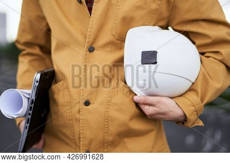 Male In Orange Jacket Standing And Holding Hardhat, Laptop And Blueprints On Construction Site. Fore
