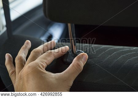 Hand Adjusts Headrest In Car Interior. Adjusting The Seat Position In The Car