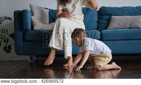 The Cute Baby Boy Playing On The Floor With A Car, While Mother Or Nanny Surfing In Your Smartphone