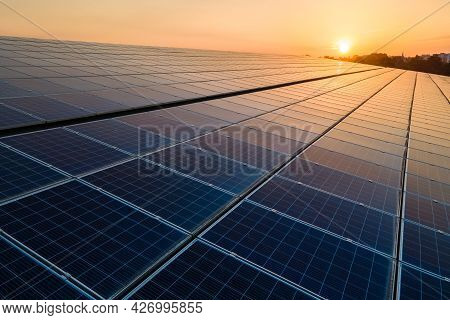 Blue Photovoltaic Solar Panels Mounted On Building Roof For Producing Clean Ecological Electricity A