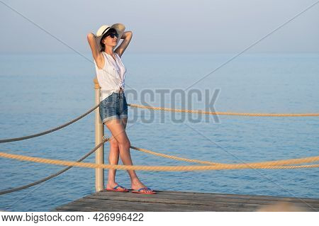Young Woman In Casual Outfit Relaxing On Seaside On Warm Summer Day.