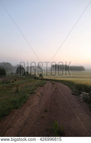 Picturesque Field And Scenic Road In The Countryside At Sunrise In Summer
