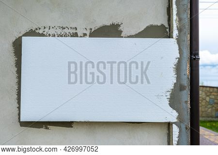 Installation Of Styrofoam Insulation Sheets On House Facade Wall For Thermal Protection.