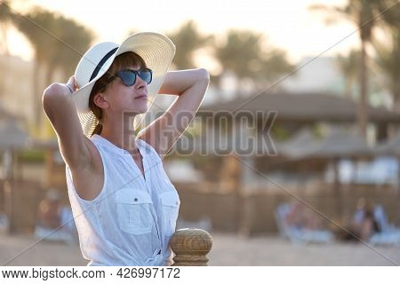 Young Woman In Casual Outfit Relaxing On Seaside On Warm Evening. Summer Vacations And Travelling Co