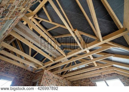 Attic Space Of A Building Under Construction With Wooden Beams Of A Roof Structure And Brick Walls.