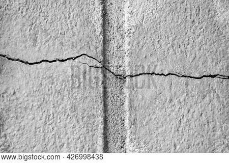 Sinuous Horizontal Thin Crack On Gray Plastered Surface Of Wall Of Old Building. Copy Space. Selecti