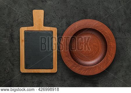 Brown Wooden Cutting Board With Slate Stone, Empty Brown Clay Plate On Black Stone Table. Top View W