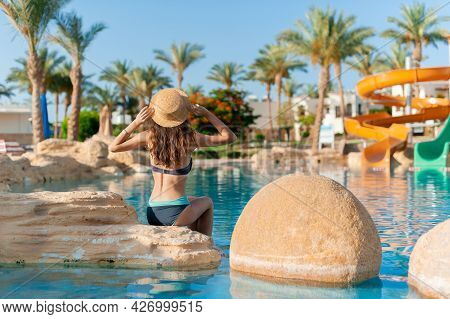 Beautiful Woman In Hat Sits On Stone Near Swimming Pool Spa. Beautiful Exotic Hotel Relax In Egypt.