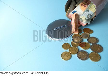 Close-up Open, Cut Tin Piggy Bank From Which Money, Cash, Euro Banknotes, Coins Spilled Out, Light B