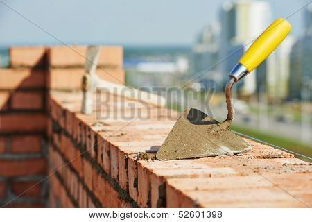 construction mason work tools. Brick trowel and pick hammer outdoors at building area