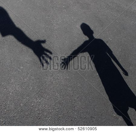 Helping Hand with a shadow on pavement of an adult hand offering help or therapy to a child in need as an education concept of charity towards needy kids and teacher guidance to students who need tutoring. poster