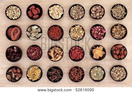 Traditional chinese herbal medicine in wooden bowls over papyrus background.