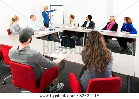 Several businesspeople meeting in a spaceous meeting room for a presentation