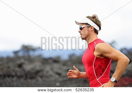 Running triathlon athlete man. Runner triathlete training for ironman on Hawaii. Young Male athlete running in red compression top on volcano in Kailua-Kona, Big Island, Hawaii.