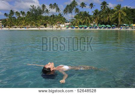 Young Woman In Bikini Floating In Clear Water