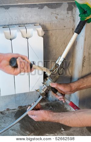 Workers crimping pipe heating system in the apartment