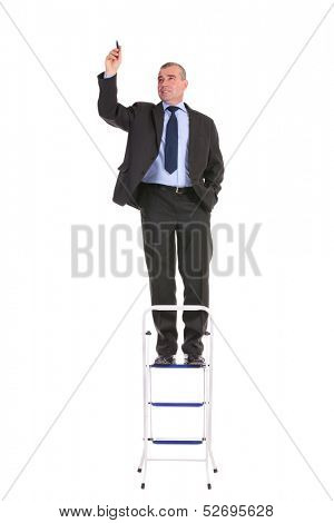 full length portrait of a business man standing on a ladder and writing while holding a hand in his pocket. on a white background