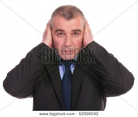 business man covering his ears while looking into the camera. on a white background