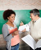 Happy male teacher gesturing thumbsup to successful student in classroom poster