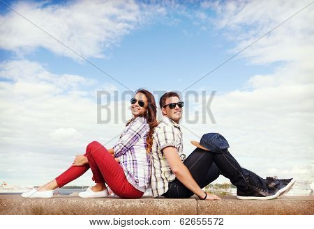 summer holidays and teenage concept - teenagers sitting back to back