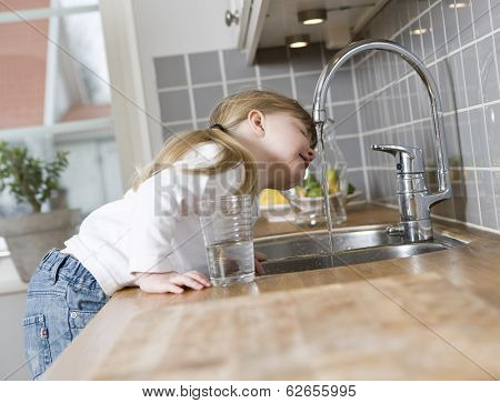Small Girl in the kitchen drinking water